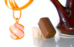 Gold chain and chocolate candy. Isolated on white Stock Photo