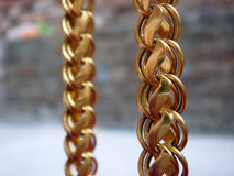Gold chain. Hanging front of wall background royalty free stock photography