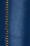 Gold chain lying on denim Stock Photo