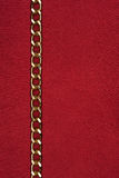 Gold chain lying on red fabric Royalty Free Stock Photography