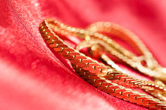 Gold chain on red cloth Stock Photos