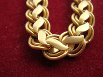 Gold chain on red surface. Sparkling gold chain on red background stock photos