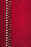 Gold chain and rhinestones lying on red fabric Stock Images