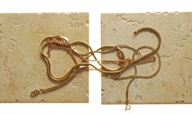 Gold chainlets lie on stone Stock Images
