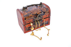 Gold chains in a closed carved wooden treasure box Royalty Free Stock Photo