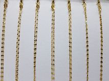 Gold chains of various sizes in a jewellery, with white background. Precious metal luxury accessories, gift and detail for celebration, shiny and golden material Stock Photography