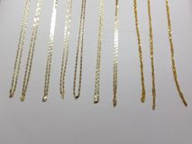 Gold chains of various sizes in a jewellery, with white background. Precious metal luxury accessories, gift and detail for celebration, shiny and golden material Royalty Free Stock Photo
