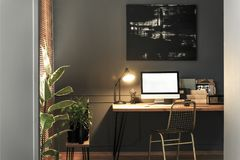 Gold chair standing by the wooden desk with lamp, notebooks and. Mockup computer in real photo of dark living room interior with modern painting on the wall stock photos