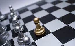 Gold chess pawn in front of white troop. Black and white chess board Stock Images
