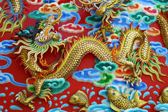 Gold chinese dragon statue at the wall of chinese temple in Thai Royalty Free Stock Photos