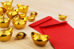 Gold Chinese ingot and Blank red envelopes on wooden background. Gold Chinese ingot Yuan Bao and Blank red envelopes on wooden background - best for Chinese New royalty free stock images