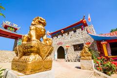 Gold chinese lion statue and Chinese style stone wall Royalty Free Stock Photo