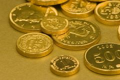 Gold Chocolate Coins. Set against a gold background Royalty Free Stock Images