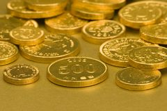 Gold Chocolate Coins. Set against a gold background Stock Image