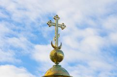 Gold Christian cross on a background of blue sky. Royalty Free Stock Images