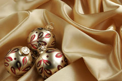 Gold Christmas Background. Gold and red ornaments on gold satin background - horizontal presentation royalty free stock images