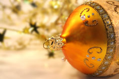Gold Christmas ball. Gold ball with small gold stars on white background Royalty Free Stock Photo