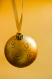Gold Christmas ball. A gold christmas ball on yellow background royalty free stock image