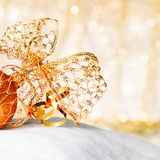 Gold Christmas ball and bow Royalty Free Stock Photos