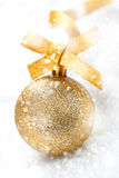 Gold Christmas ball in falling snow Stock Image