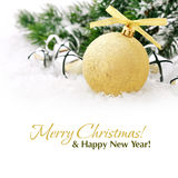 Gold christmas ball. And fir branches with decorations on snow Royalty Free Stock Images