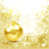 Gold Christmas ball on a golden light background. Stock Photography
