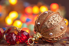 Gold christmas ball over blurred colorful background Stock Image