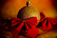 Gold Christmas ball with red bows Royalty Free Stock Photos