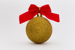 Gold Christmas ball with ribbon on white background. Royalty Free Stock Images