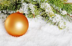 Gold christmas ball in snow Stock Images