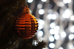 Gold Christmas ball on tree with Christmas lights Royalty Free Stock Image