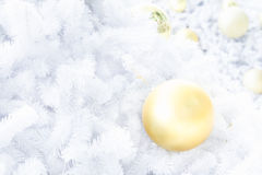 Gold christmas ball on white christmas tree Royalty Free Stock Photo