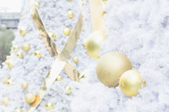Gold christmas ball on white christmas tree Royalty Free Stock Photography