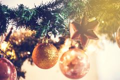 Gold Christmas balls decoration in tree, beautiful sparkles close-up