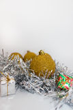 Gold Christmas balls and gifts on shiny silver tape on white background Stock Photo