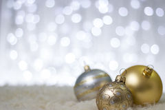 Gold Christmas balls. Photography of gold and silver Christmas balls in a winter scene. Beautiful Christmas Decorations. Close-up image with Gold, Silver