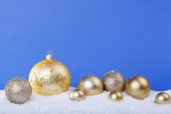 Gold Christmas balls in the snow Stock Images