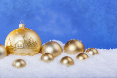 Gold Christmas balls in the snow Royalty Free Stock Images