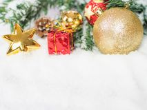 Gold christmas balls and star and red box in the snow. Copy and Stock Photos