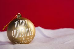 Gold Christmas bauble on the snow, copy space, red background. Gold Christmas bauble on the snow, copy space red background Royalty Free Stock Photo