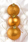 Gold Christmas baubles. Three gold Christmas baubles on white silk stock image
