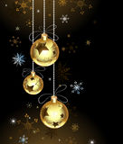 Gold Christmas baubles. On a brown background with snowflakes Royalty Free Stock Images
