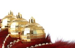 Gold Christmas baubles on fur. Three gold Christmas baubles lying on fur with gold beads isolated on white background with copy space. Shallow depth of field Royalty Free Stock Photography