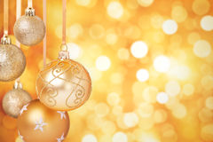 Gold Christmas baubles hanging in front of a gold background Stock Images