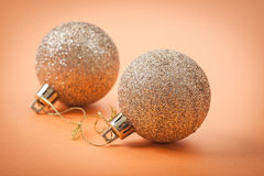Gold christmas baubles on light brown background Royalty Free Stock Image