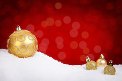 Gold Christmas baubles on snow with a red background Stock Photos