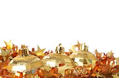 Gold Christmas baubles on tinsel Royalty Free Stock Images