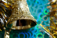 Gold christmas bell. On a green background close up Stock Image
