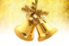 Gold christmas bells. A pair of christmas decorations. Gold bells with ribbon,on grunge texture background Stock Images