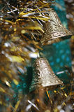 Gold christmas bells. On a green background close up Royalty Free Stock Photography